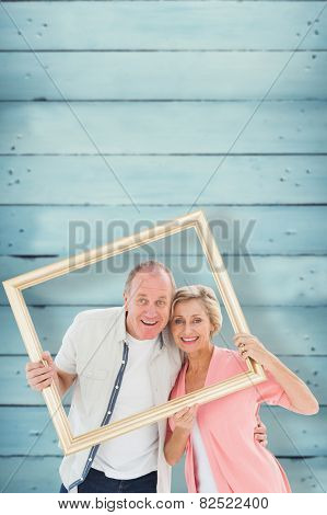 Older couple smiling at camera through picture frame against wooden planks