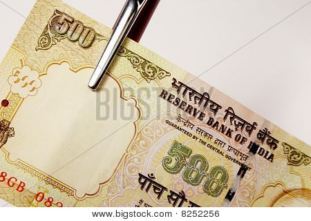 single 500 rupee indian currency note with a pen
