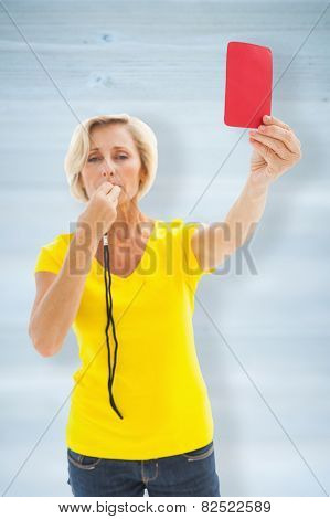 Mature blonde showing red card to camera against wooden planks