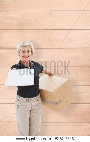 Happy delivery woman looking for signature against wooden planks