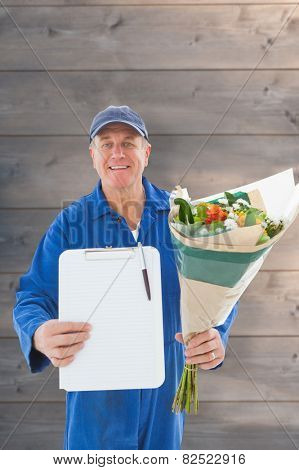 Happy flower delivery man showing clipboard against wooden planks