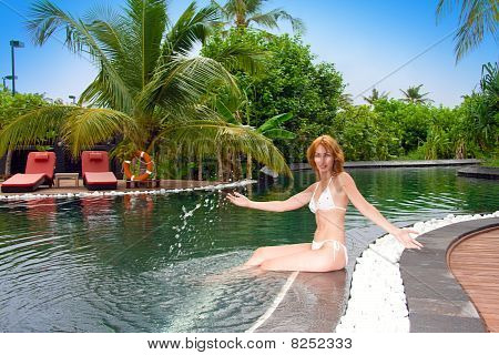 Young pretty woman in pool in tropical garden