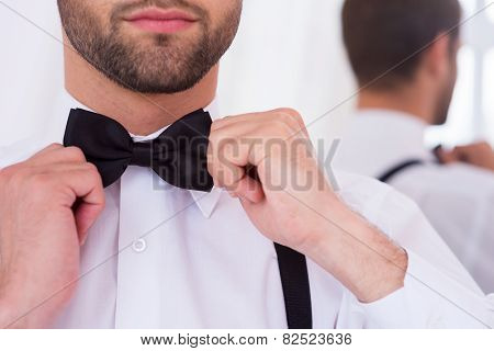 Adjusting His Bow Tie.