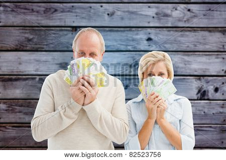 Happy mature couple smiling at camera showing money against grey wooden planks