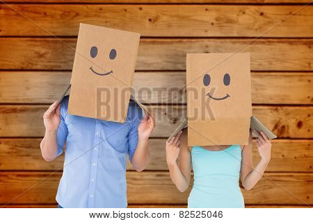 Couple wearing emoticon face boxes on their heads against wooden planks background