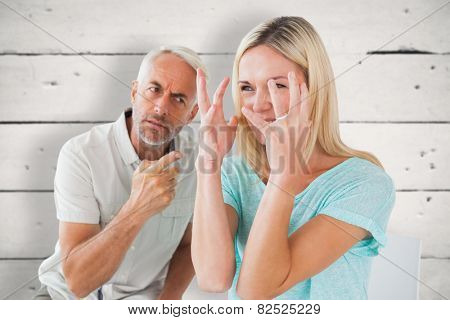 Unhappy couple sitting on chairs having an argument against white wood