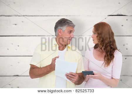Casual couples working out their bills against white wood