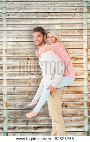 Handsome man giving piggy back to his girlfriend against wooden background in pale wood