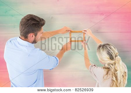 Attractive young couple hanging a frame against pink and green planks
