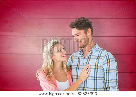 Attractive young couple smiling at each other against wooden planks background