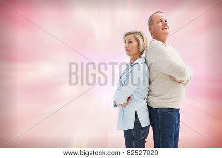 Mature couple standing and thinking against digitally generated pink girly design