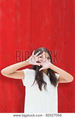 Fearful brunette covering her face against red wooden planks