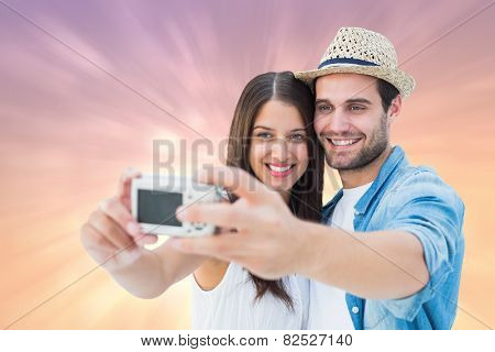 Happy hipster couple taking a selfie against pink abstract light spot design