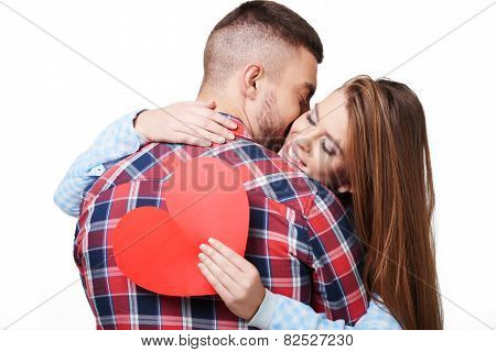 Young man kissing woman with heart card