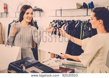 Happy customer with shopping bag in fashion showroom