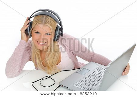 Pretty Young Girl Listening And Singing To The Music With Headphones From Her Laptop. Isolated On Wh