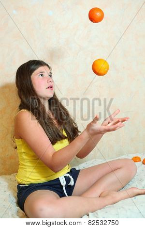 Pretty Teenager Girl With Long Dark Hair Jugglering With Tangerines
