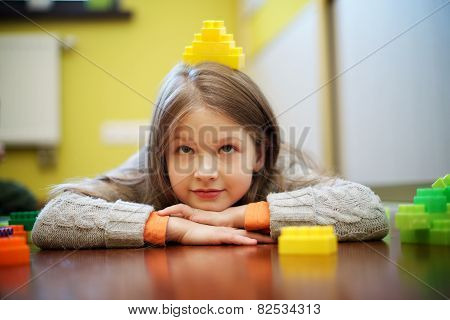 Happy beautiful girl plays with blocks