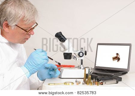 Police forensic technician in a laboratory, dusting a gun for finger prints and comparing spent bullets.
