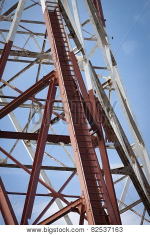 Metal ladder rungs of a red and white radio antenna tower against a blue sky background.