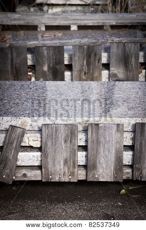 Sheets of gray granite stone slabs stacked up with wooden supports on the sides.
