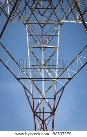 Close up of the metal frame of a red and white radio antenna tower against a blue sky background.