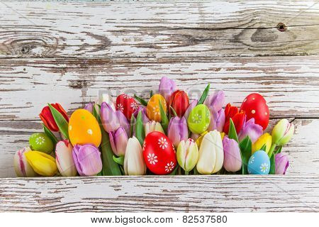 tulips and easter eggs on wooden background, close-up.