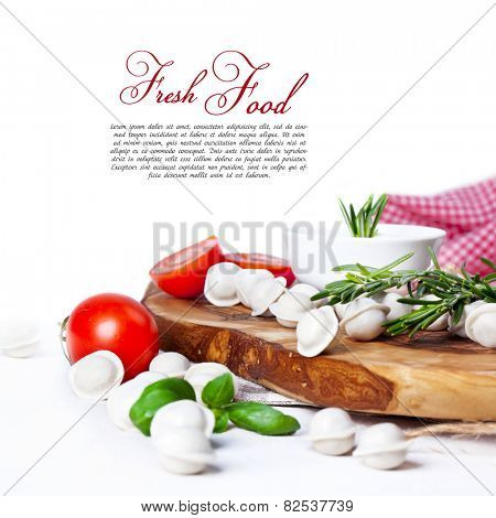 Tortellini and vegetables on white wooden background