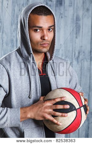 Image of fit young afro american athlete holding a basketball looking away with copyspace. Muscular