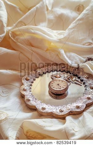 Antique pocket watch on mirror lying on a wedding dress