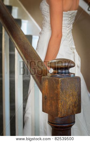 Bride walking up old oak staircase