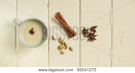 Top view of a chai tea with cinnamon, anise and cardamom on a white wooden background