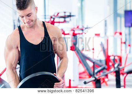 Man taking weights from stand in fitness gym preparing for training