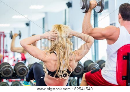 Friends, man and woman, lifting weights in fitness gym, she is doing sit-up for flat stomach
