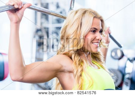 Girl at back fitness machine training in gym for bodybuilding
