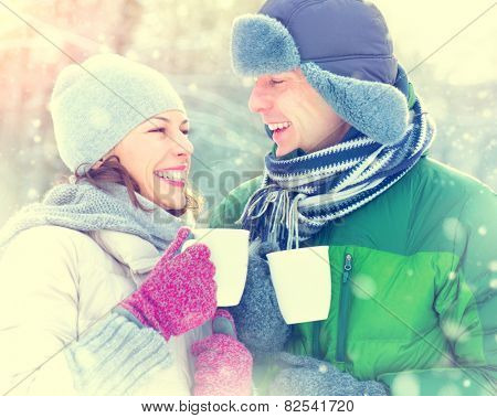 Happy Winter Couple drinking hot beverage outdoors. Having Fun in winter park. Snow. Winter Vacation. Hot Drink Outdoor. Joyful family. St. Valentine's Day celebration. Toned photo