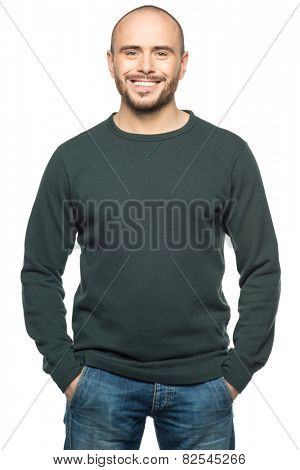 Studio portrait of happy young man in casual wear with hands in pockets, isolated on white background