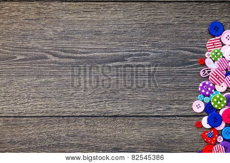 background of a wooden board and sewing buttons
