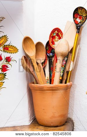wooden spoons painted in Khokhloma style in clay bowl