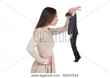 strict young woman looking at small man. isolated on white background