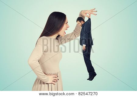 aggressive young woman holding small man and screaming at him. photo over blue background