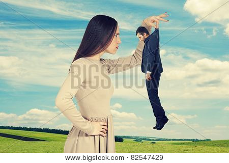 serious young woman looking at small man over sky and green field