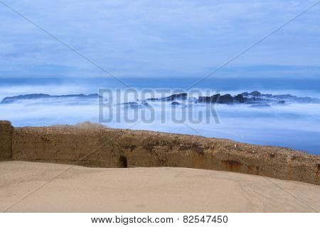 A seawall separates the rough ocean from a sandy beach during an early morning sunrise
