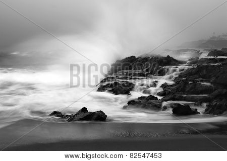 An early morning slow motion images of seawater rushing over sharp, rugged shoreline reef in Laguna Beach, California.