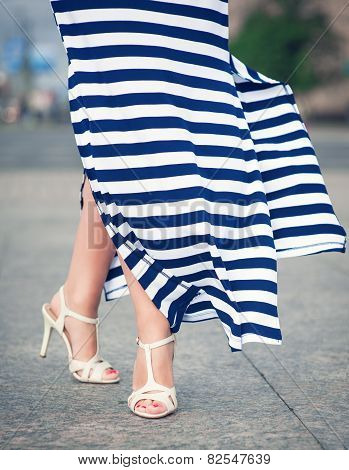 Legs Of Woman Dressed Long Fluttering Striped Dress