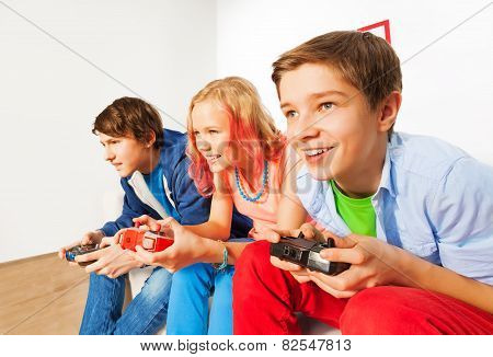 Three friends with joysticks playing game console