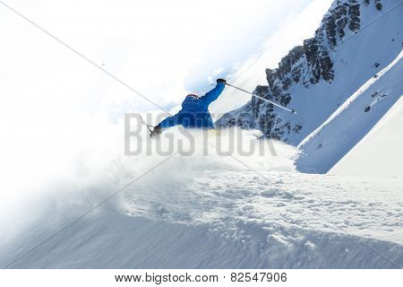 Male skier on downhill freerider with sun and mountain view