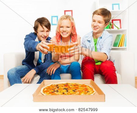 Positive teens holding glasses with juice on sofa