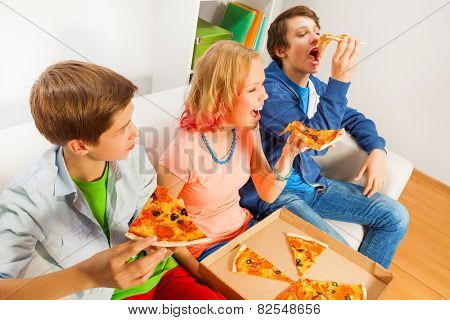Happy teens eating pizza pieces together at home