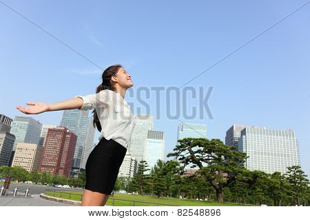 Freedom success businesswoman - Tokyo japanese city skyline. Happy carefree business asian mixed race woman arms open up in the sky, Japan.